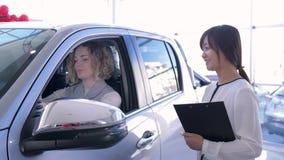 工作者汽车修理店画象与在陈列室时显示在汽车里面的钥匙,当购买汽车的女孩消费者的 股票视频