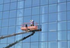 工作者洗涤在摩天大楼的玻璃门面的Windows,站立在起重机的平台 图库摄影