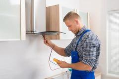 工作者测试有多用电表的厨房敞篷 库存照片