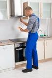 工作者测试有多用电表的厨房敞篷 免版税库存图片