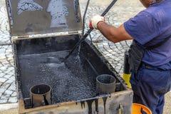 工作者混合参加熔化的沥青的锅炉 免版税库存图片