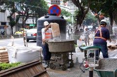 工作者混合的水泥的行动准备的在路的建造场所 图库摄影