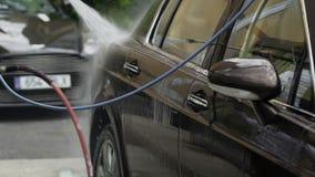 工作者清洁汽车,在车,成功的洗车事务的喷洒的水 股票录像