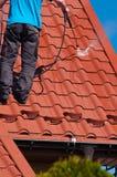 工作者清洁金属屋顶用高压水 免版税库存照片