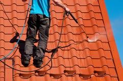 工作者清洁金属屋顶用高压水 免版税库存图片