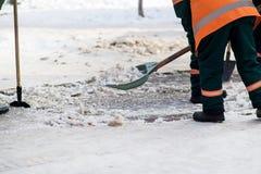 工作者清洗雪铁锹 免版税库存照片