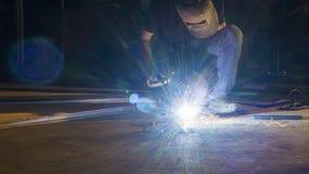 工作者焊接金属,在锋利的火花一刹那灯光管制线, i的焦点 免版税库存照片