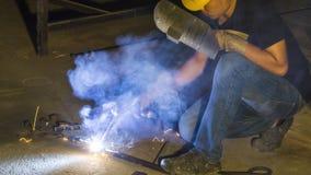 工作者焊接金属,在锋利的火花一刹那灯光管制线, i的焦点 库存照片
