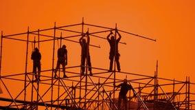 工作者现出轮廓在日落建造者收集设计 建筑工人概念大厦剪影人减慢 股票录像