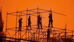 工作者现出轮廓在日落建造者收集设计 建筑工人概念大厦剪影生活方式人 影视素材