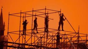 工作者现出轮廓在日落建造者收集设计 建筑工人概念大厦生活方式剪影人 股票录像
