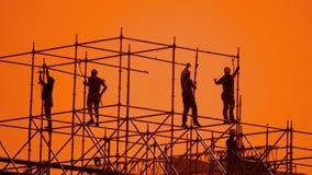 工作者现出轮廓在日落建造者收集设计 生活方式建筑工人概念大厦剪影人 股票录像
