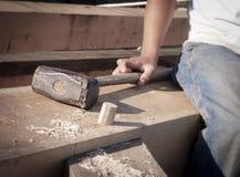 工作者的手和大锤在Timberframe联接的Restng 免版税库存照片