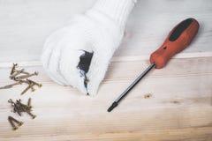 工作者的手在与螺丝刀的一个木块拧紧 库存图片