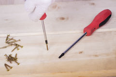 工作者的手在与螺丝刀的一个木块拧紧 免版税库存图片