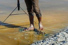 工作者的脚由在盐农场的盐包括桑珀尔盐湖的 r ?? 免版税库存照片