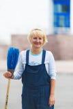 工作者的画象清洁有笤帚工具的城市街道 免版税库存照片
