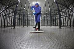 工作者统一清洁楼层在仓库 免版税库存图片