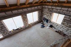 工作者脚手架的衣裳、零件和在地板上的建筑材料在改造期间,整修,引伸 免版税库存照片