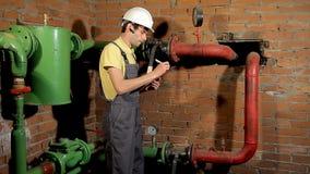 工作者记录测压器的读书在剪贴板的 热化网络的工程师检查 股票视频