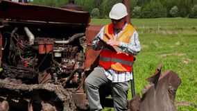 工作者谈话在巧妙的电话在残破的推土机附近 股票视频