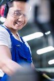 工作者运行的金属跳在工厂 免版税库存照片