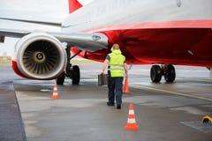 工作者运输交通锥体和塞子乘飞机在跑道 免版税库存图片