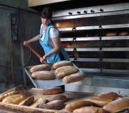 工作者采取面包在熔炉外面 图库摄影