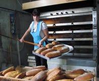 工作者采取面包在熔炉外面 库存图片