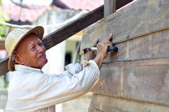工作者钉牢与锤子木地板 免版税库存照片