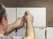 工作者铺磁砖工投入陶瓷砖 免版税库存照片