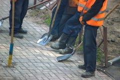 工作者队在沿电车car& x27的一条街道上把热的沥青放; s铁路线 库存图片