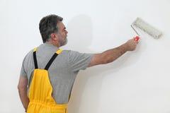 工作者绘画墙壁在屋子里 免版税库存图片