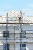 工作者建造者推力在脚手架的建筑材料 免版税库存照片