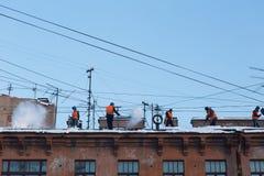 工作者从雪清洗屋顶 免版税库存照片