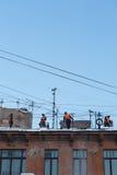 工作者从雪清洗屋顶 库存图片