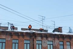 工作者从雪清洗屋顶 库存照片