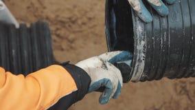 工作者squize在手指的胶粘剂在手套并且应用它在塑料管子边缘  股票视频