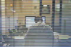 工作通过窗口被看见的已故的商人人剪影  库存图片