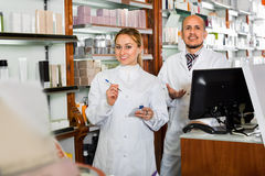 工作配药商店的女性和男性药剂师 免版税库存照片