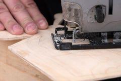 工作金属制品车间在木头的困难的形式切口的一把电竖锯 图库摄影