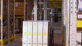 工作铲车在仓库里 有箱子乘驾的铲车在行之间在仓库里 工业内部 股票录像