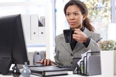 工作饮用的茶的蓬松卷发女实业家 免版税库存照片