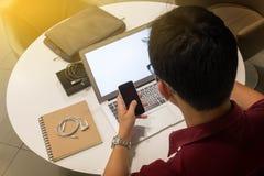 工作从家的一个年轻人的播种的射击使用巧妙的电话 图库摄影