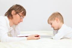 工作从家的父亲和儿子 免版税库存图片