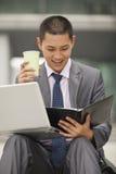 工作年轻的商人微笑和户外,拿着咖啡杯 免版税库存照片