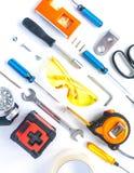 工具、板钳、螺丝刀、水平、卷尺、螺栓和安全玻璃顶视图在白色背景 免版税库存照片