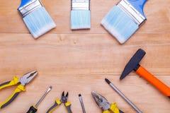 工具和刷子在木背景的一个圈子在 在视图之上 免版税库存图片