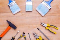 工具和刷子在木背景的一个圈子在 库存图片