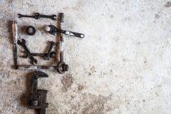 工具和零件安排了以在水泥的一张兴高采烈的面孔的形式 库存照片
